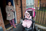 Seanalee, 17, smokes a cigarette while her daughter Olivia Rose, sits in a stroller at the front door of their home in the Catholic Ardoyne area of north Belfast. After having her baby, Seanalee dropped out of school but she hopes to return next year.
