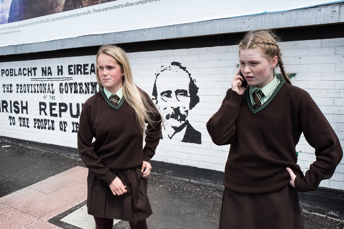 After school, Tigernach (right), 14 and her friend Dawn, 13, wait for a green traffic light to cross the road in the Catholic Falls road area of west Belfast. Behind them a mural commemorating the 1916 Proclamation of the Republic, a document written in the name of the self-styled Provisional Government of the Irish Republic that proclaimed Ireland's independence from the United Kingdom.
