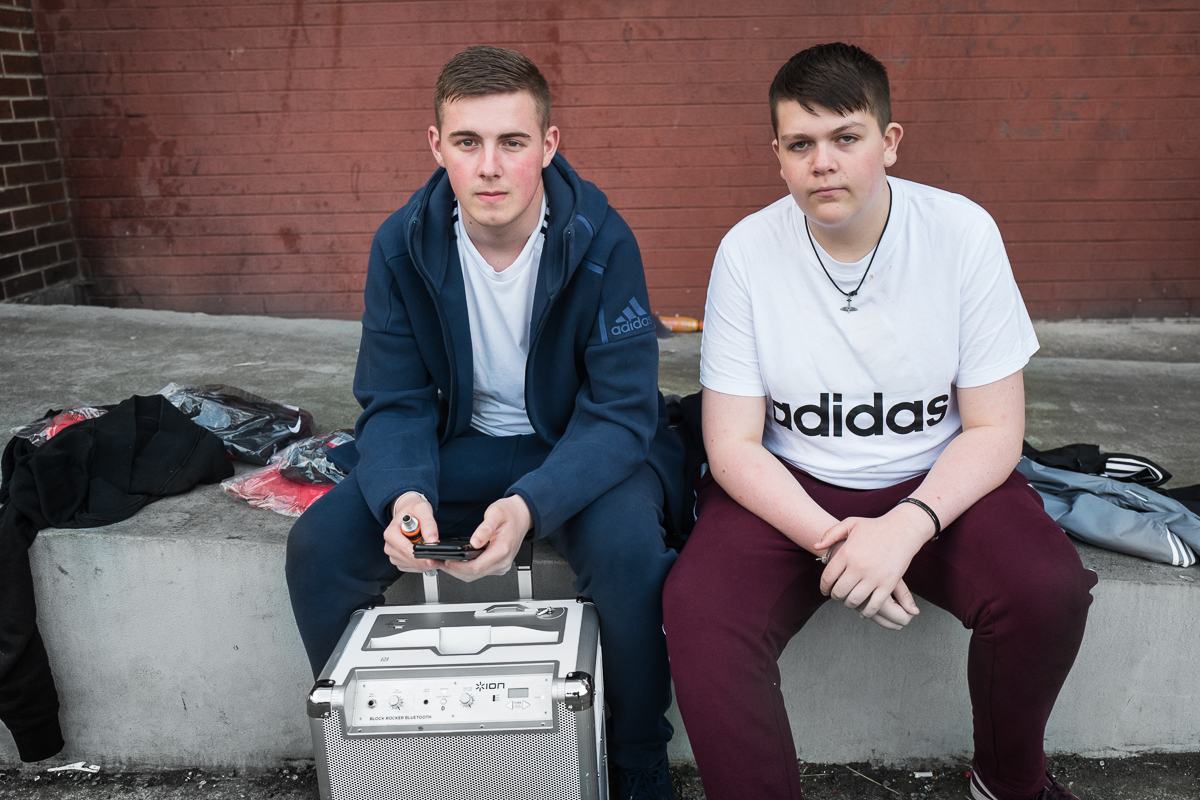 Lewis (left), 16, and Daniel, 15, sit outside the Corpus Christi Youth Centre in the Catholic Upper Springfield area of west Belfast. The youth center organizes a cross-community project in which youths from both communities participate. Few opportunities to socialize and interact make it difficult to have real friends in the other community. Cross-community activities have only a limited impact as at the end of the activities, young people return to their segregated neighborhoods.