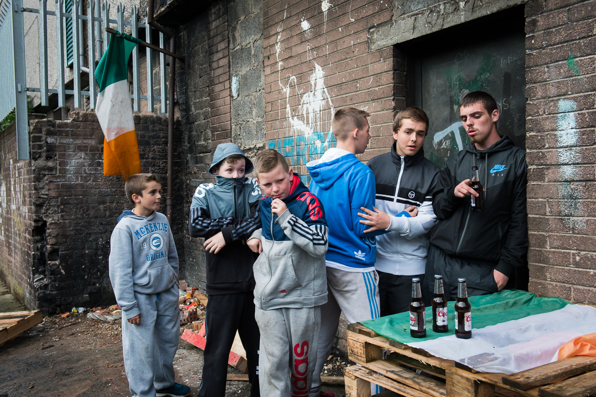 Surrounded by Irish flags, teenagers hang out in the Catholic New Lodge area of north Belfast. The tricolor flag, the national flag of the Republic of Ireland, is a symbol of republicanism. North Belfast is among the most socially and economically deprived areas in northern Ireland. It was also an area that experienced some of the worst violence. A large part of its population has been directly affected by the Troubles and the area remains deeply divided.