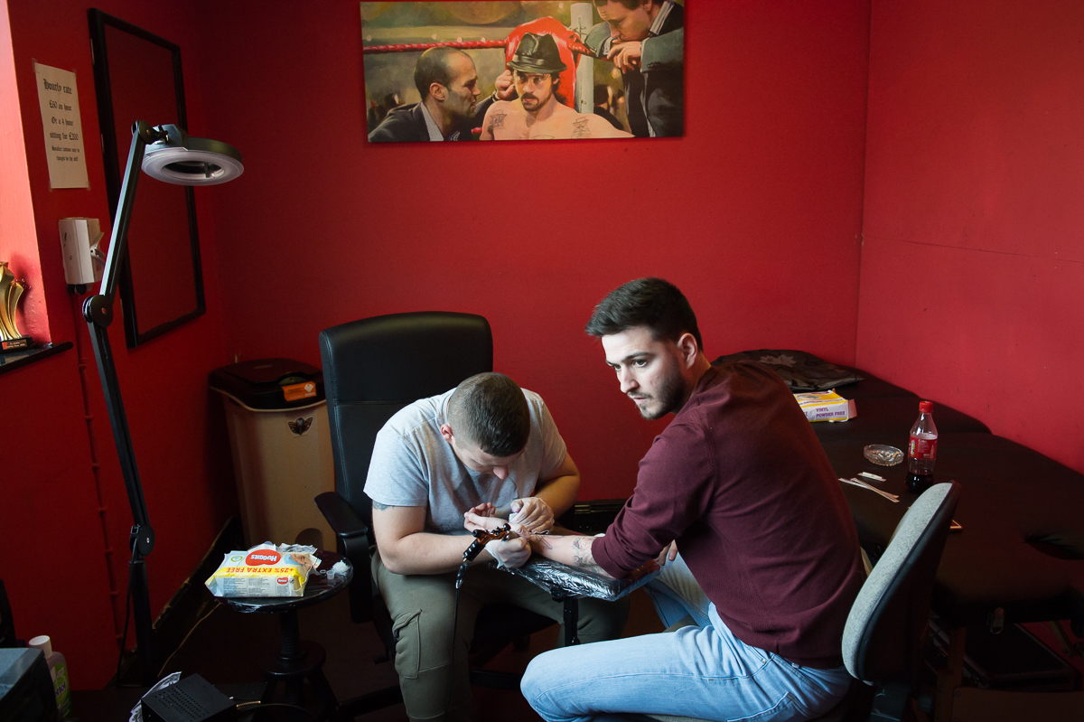 A young man gets a tattoo on the Catholic Falls Road in west Belfast.  Fear of being identified as belonging to {quote}the other{quote} community limits young people's movement and activities and reduces their educational, economic and cultural opportunities.
