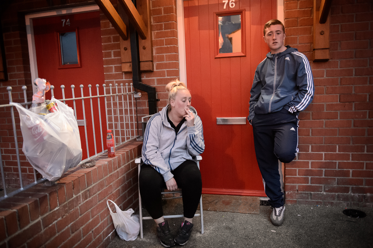 Ashley, 26, smokes a cigarette outside her home while her boyfriend's brother Dylan, 16, stands next to her in the Protestant Lower Shankill estate in west Belfast. Ashley's family was heavily involved in the UDA (Ulster Defence Association), a loyalist paramilitary group. During the feuds among different factions of the UDA in 2001 her family was expulsed by another faction and they now live in England. After some time Ashley and her mother were allowed by the paramilitaries to come back.