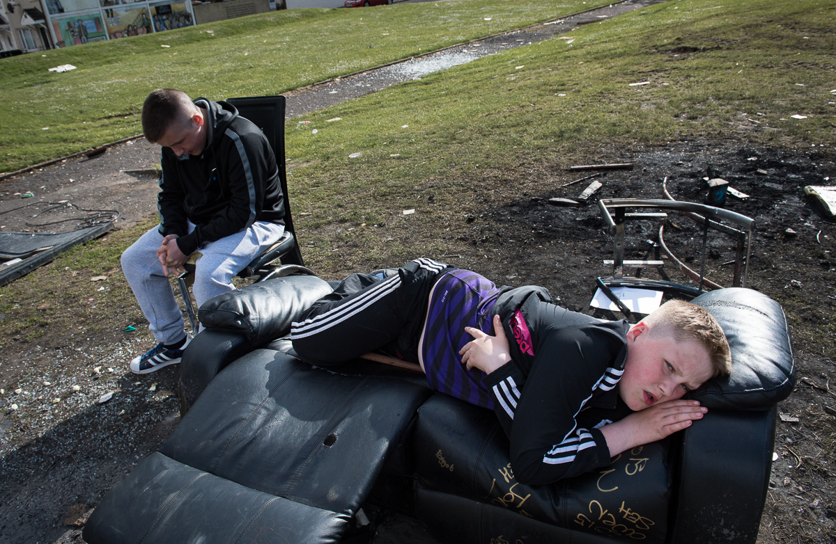 Young people hang out on discarded furniture in  the Protestant Lower Shankill area of west Belfast. Working-class youth from both communities grow up in a risk-laden environment where they are exposed to poverty, barriers and paramilitaries.