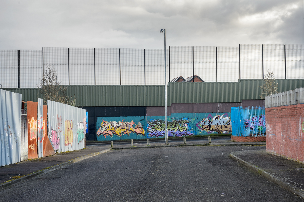 Graffiti on a section of the so-called peace wall along Cupar Way in west Belfast, as seen from the Protestant side. The eight-meter-high concrete and corrugated iron partition separating Catholic Falls and Protestant Shankill areas of west Belfast, is the city's oldest and most imposing segregation wall. First built in 1969 as a temporary solution to reduce violence, the peace walls — a euphemism for segregation barriers — have increased in number and scale since the start of the peace process. The barriers take many forms: Not only walls but also fences, gates, roads and empty buffer zones divide the Catholic and Protestant communities in some of the city's most economically deprived areas. The government promised to take the barriers down by 2023, but many residents are not ready for them to come down any time soon. Not all interface areas — the common boundary between a Protestant and a Catholic area —  have a physical border. Sometimes there is only an invisible dividing line that local people are aware of.