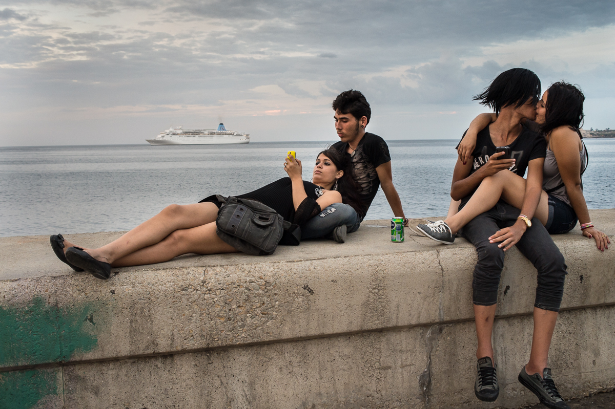 Malecón, Havana   On a Saturday night, seventeen-year-old Adams Balboa, Rachel Ortega, Julio Richard and Beatriz Regla hang out along the Malecón, Havana's seawall, while a cruise ship carrying foreign tourists, is leaving the harbor. The increasing number of tourists coming to the island will likely  increase the division between rich and poor on the island. Cubans, who don't have the money to set up a private business to provide services to the tourists, risk to be left out.