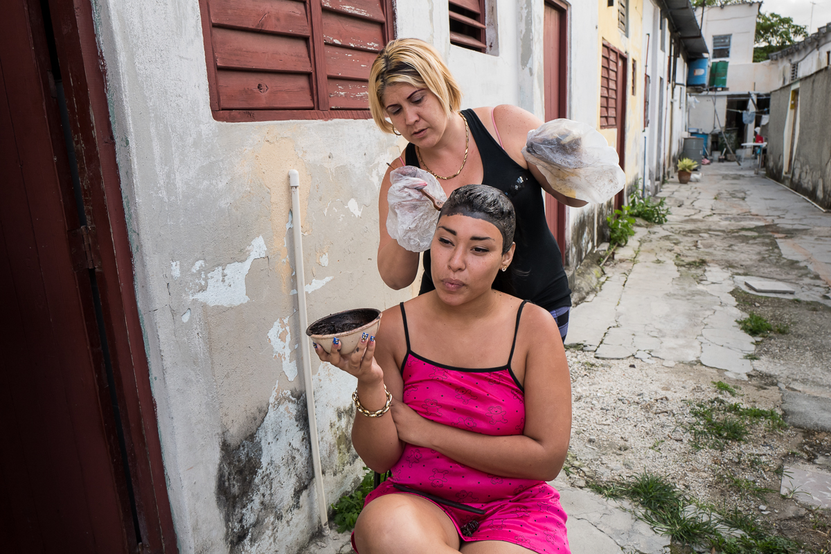 Regla, Havana   Arianna Gusmán Peña , 19, gets her hair dyed by a neighbor in the municipality of Regla. {quote}We don't have much{quote} she said but we have solidarity, we help each other{quote}.