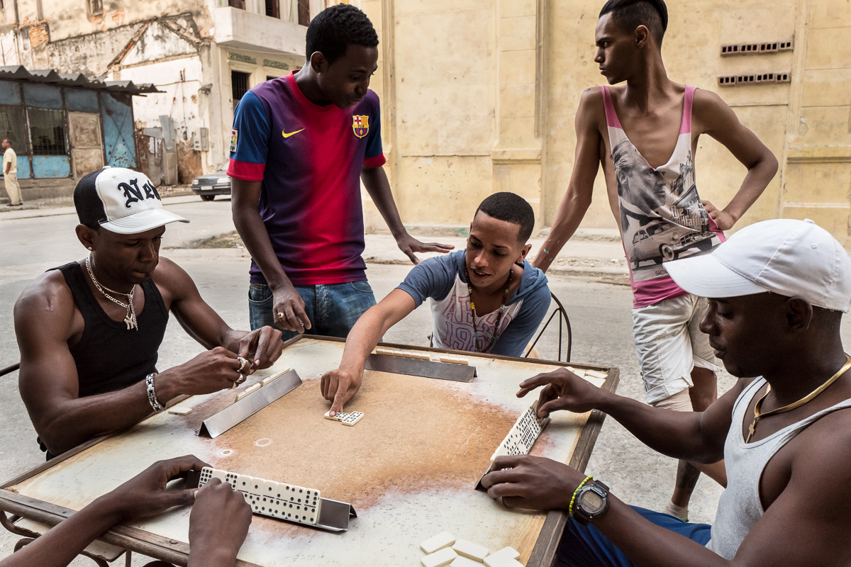 Centro Habana, Havana   Young men play dominoes in the streets of the Centro Habana neighborhood. Many young people dream of leaving the island -often to the United States- and have a fascination with American icons.