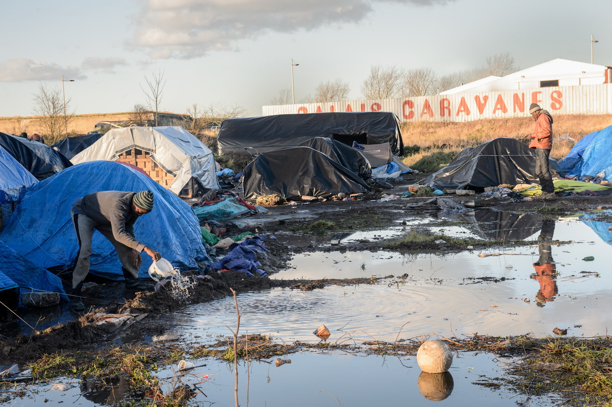 "Calais, December 2014 A Sudanese migrant tries to keep his tent dry in the so-called ""Sudanese jungle"". The makeshift tent and tarpaulin camps in the Calais area are known as {quote}jungles{quote}."
