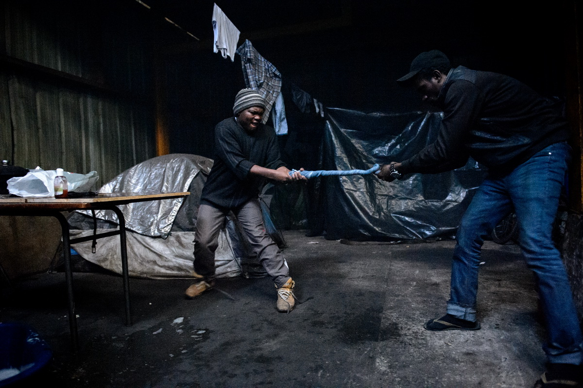 Calais, December 2014 Sudanese migrants wring out laundry before hanging it to dry in the cold, and damp  hangar on the squatted Galoo site, a large abandoned metal recycling plant.