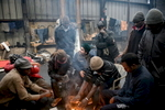 Calais, December 2014 Sudanese migrants warm themselves over a fire in the cold, damp and smoke-filled Galoo squat, a large abandoned metal recycling plant.
