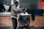 Calais, December 2014 Sudanese migrant Mohammed (22) cuts the hair of a fellow migrant in Galoo squat, a large abandoned metal recycling plant.