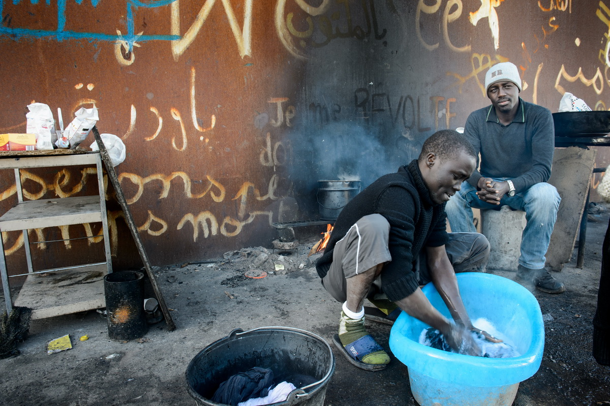 """Calais, December 2014 Mustapha (29), a Sudanese statistician washes his clothes on the squatted Galoo site, a large abandoned metal recycling plant.  Mohammed (28), a management graduate,  sits next to him. Both men come from Darfur and met on the boat to Italy. Mustapha explained """"the boat trip from Egypt to Calabria in Italy took 24 days. It was a nightmare. The people smugglers only gave us half a glass of water and some dry bread per day."""""""