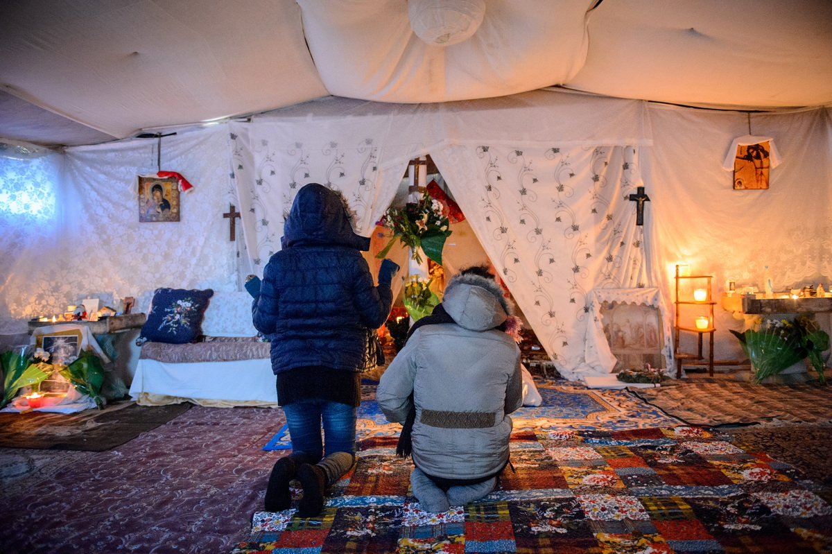 Calais, December 2014 Eritrean women pray in a makeshift church set up by the Eritrean community in the Tioxide jungle camp.