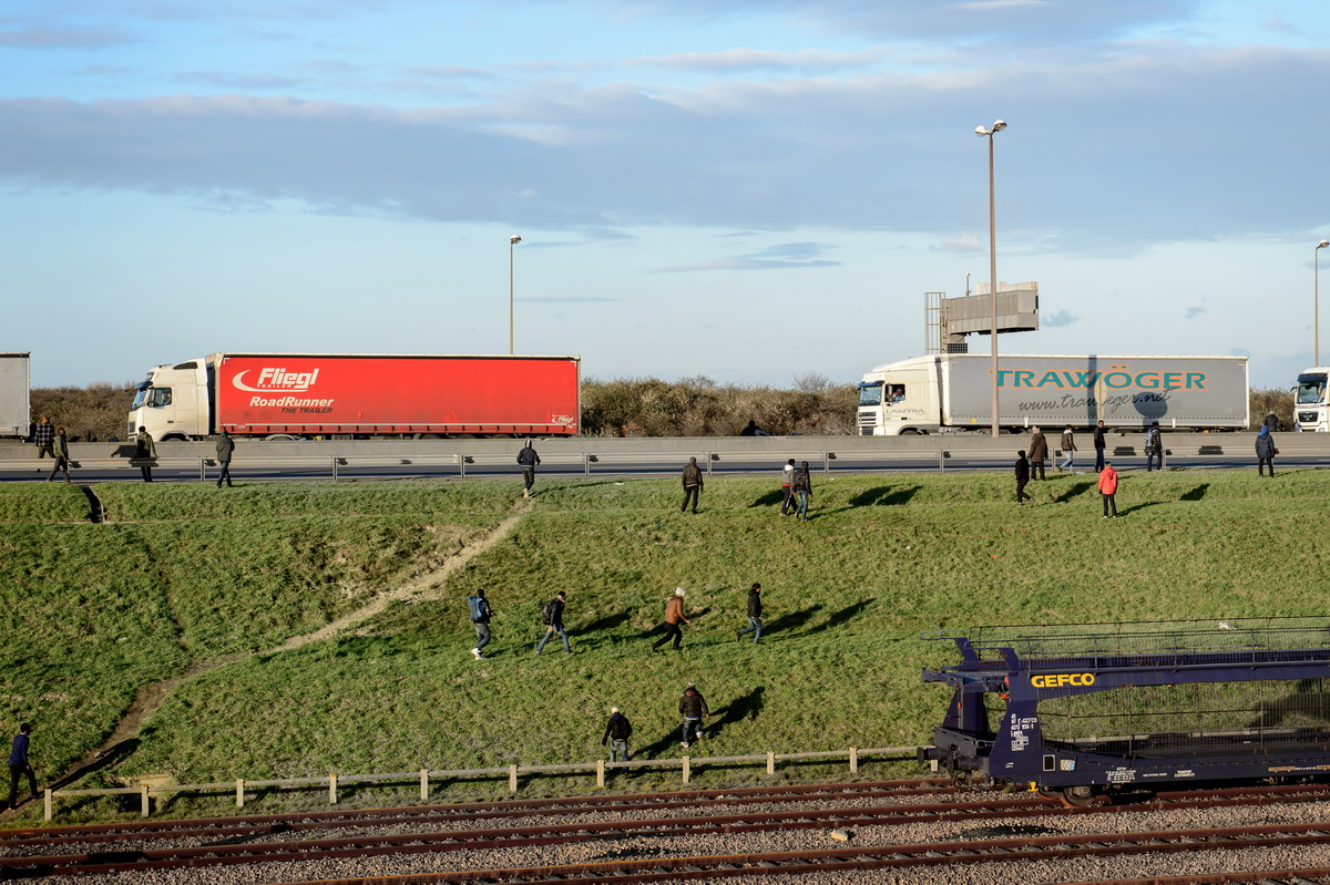 Calais, December 2014 Hoping to board a lorry, migrants run towards a traffic jam on the motorway towards the ferry port.