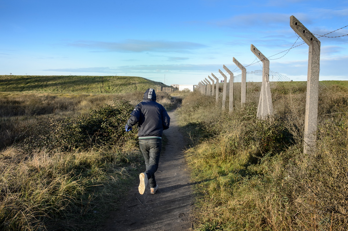Calais, December 2014 A migrant runs from the Tioxide jungle camp towards the motorway after having been alerted by other migrants of a traffic jam in the direction of the ferry port. Migrants try to stow away on the lorries while these are slowed down.