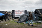 Calais, December 2014 Migrants walk by shelters made of plastic sheeting, packing crates and other found materials in Tioxide camp in Calais. The makeshift tent and tarpaulin camps are locally known as {quote}jungles{quote}.  The Tioxide jungle, situated next to a chemical plant, is currently the largest camp in Calais.