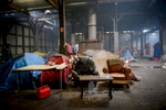 Calais, December 2014 Inside the Galoo squat, a large abandoned metal recycling plant, housing hundreds of migrants.