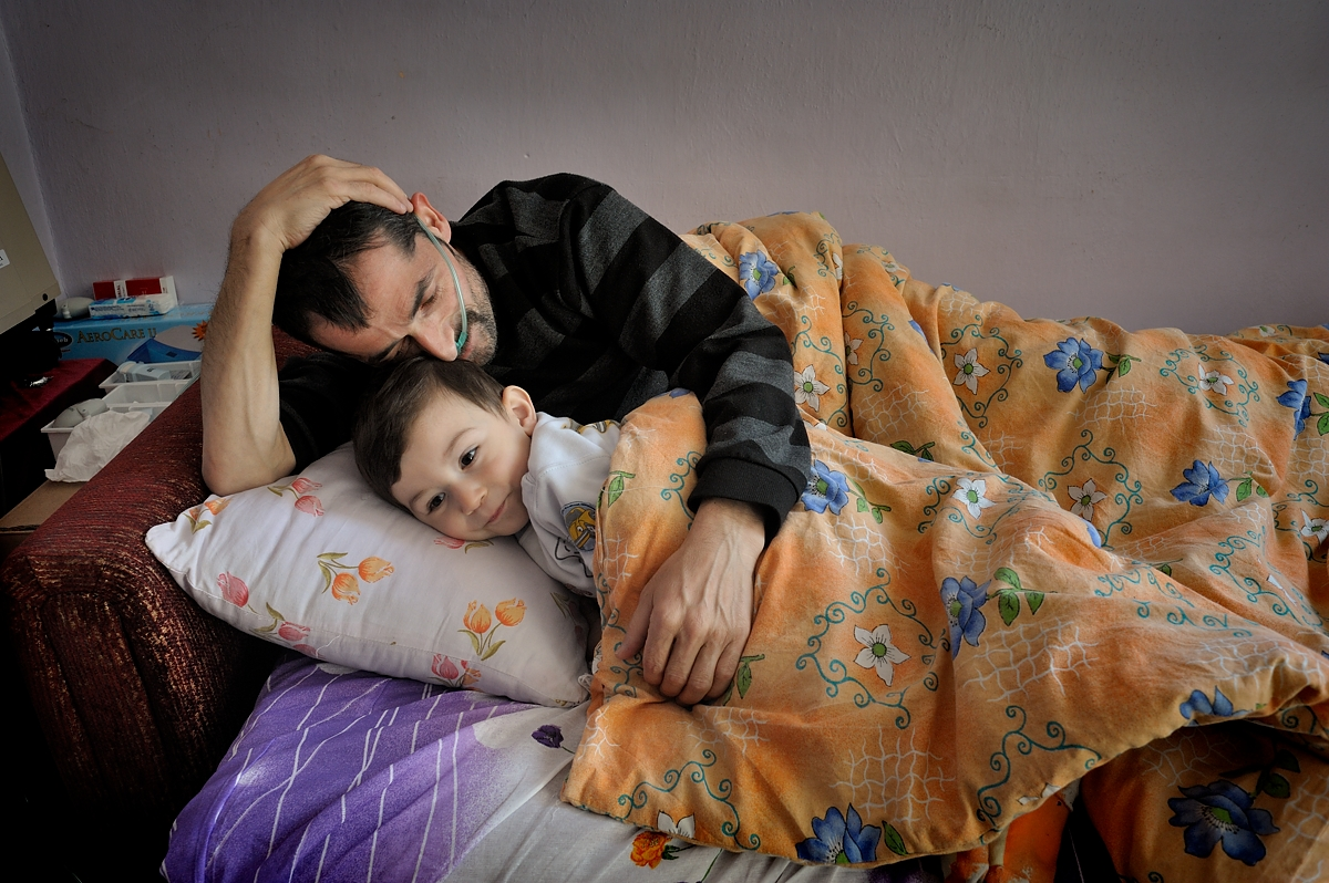Thirty-year-old Mehmet Çalis lies in bed with his nephew Faruk.  Before becoming ill with silicosis at the age of twenty-four, Mehmet worked for less than one and a half year in the sandblasting industry.