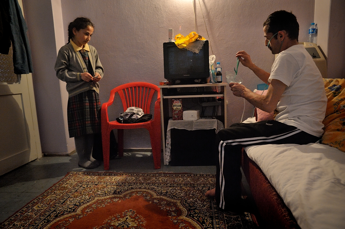 Mehmet puts on his oxygen mask while his younger sister Gülsüm looks on. Mehmet lives with his extended family in the working class neighbourhood of Gaziosmanpasa in Istanbul. Like many who ended up working in the sandblasting industry in Istanbul, the family came from a poor region in eastern Turkey looking for work.