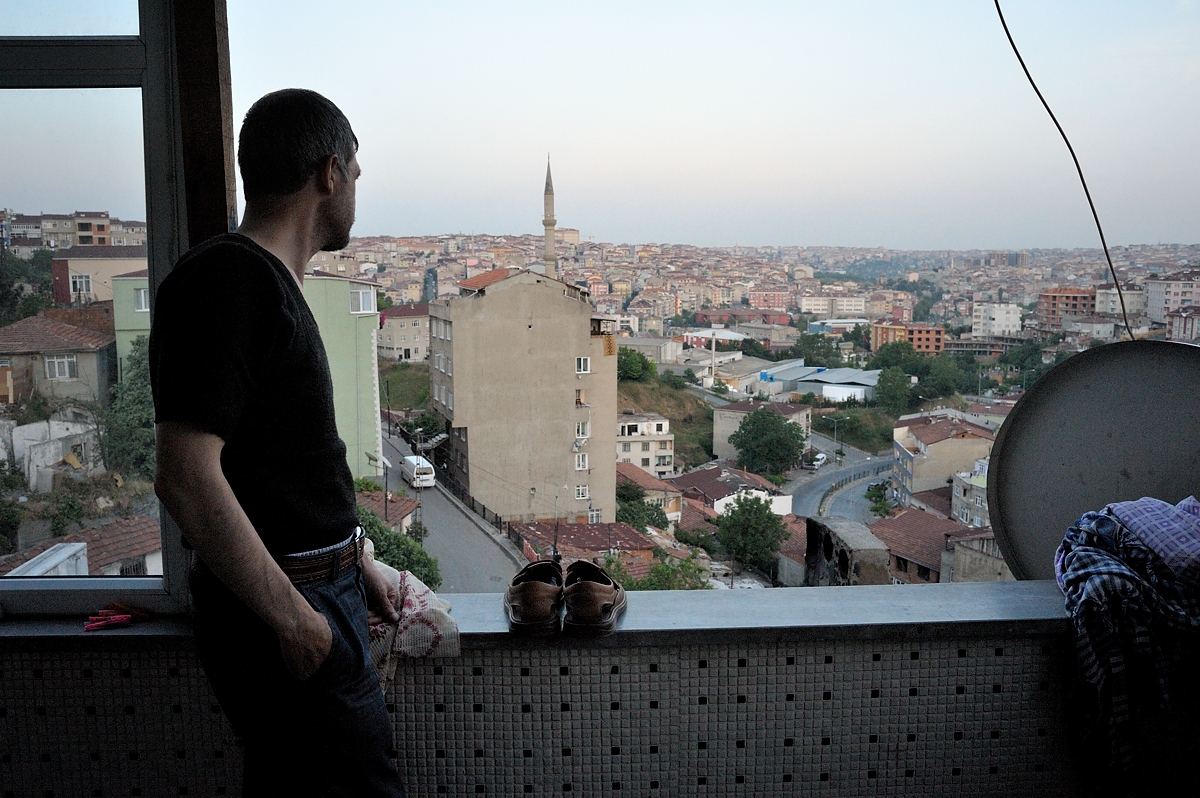 Bekir stands on the balcony of his apartment in the working-class neighbourhood of Gaziosmanpasa in Istanbul. From his balcony he looks over the textile factory where during ten years he worked six days a week for a minimum of twelve hours a day.