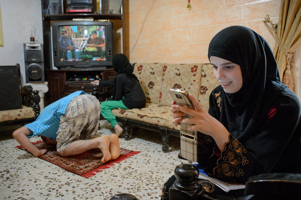 Sara Abed El Hade (16) checks the messages on her smartphone while her father Ahmed prays and her younger sister Amina watches television. Sara wants to become a graphic designer.
