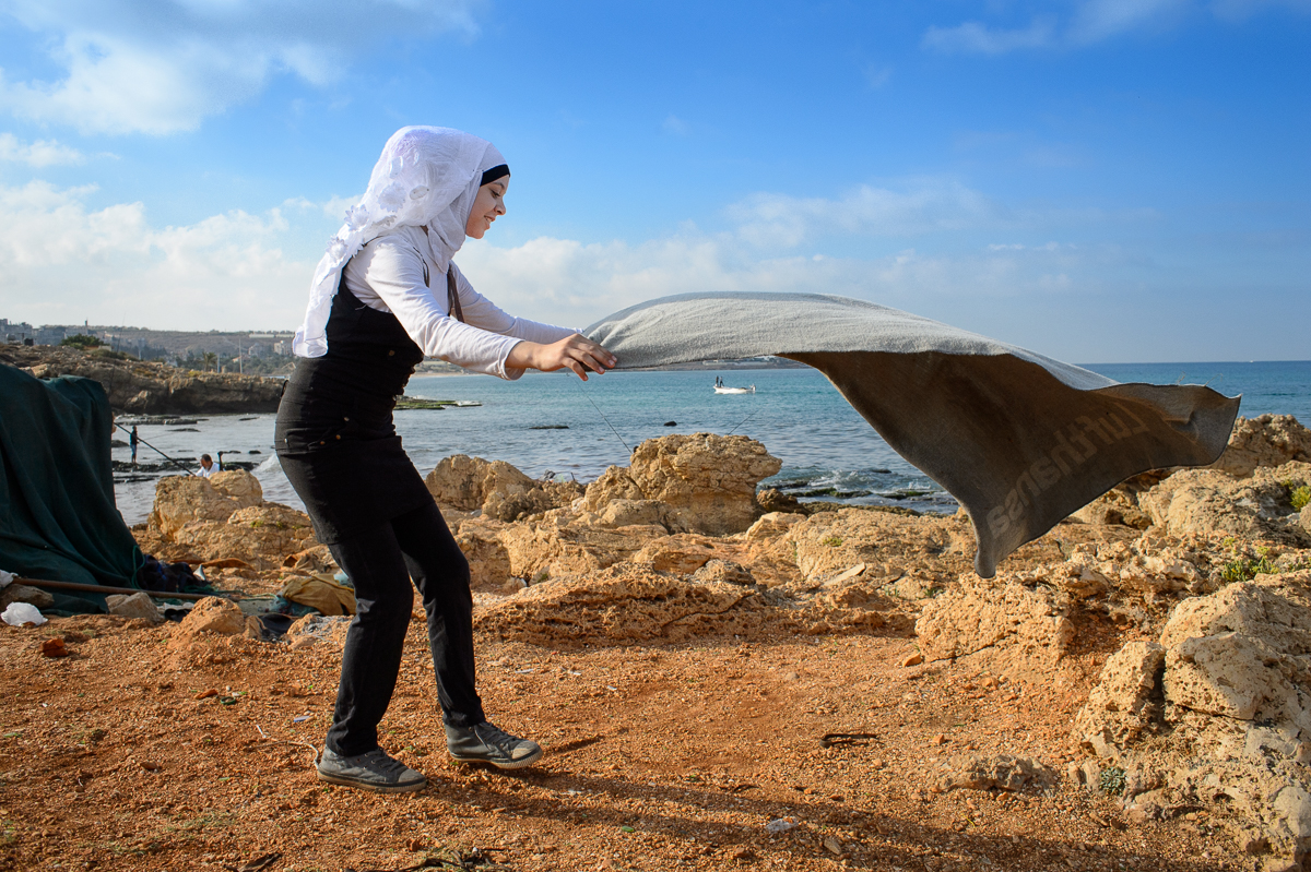 On a rare outing with her family, Marwa Hazineh(13), a Palestinian refugee from Syria, spreads out a blanket at the beach in Ouadi Al Zeyneh. She lives with her family in a two-room windowless apartment in Shatila.