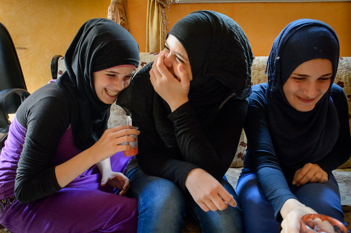 Sisters Sarah (16) and Fatima (17) Abed El Hade share a laugh with Fatima Gazzawi (16) at their apartment.