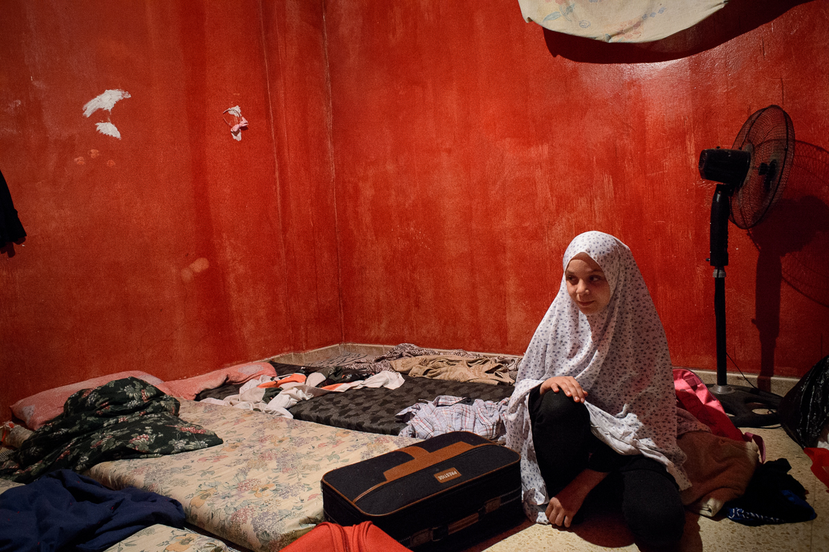 Marwa Hazineh (13) sits in the windowless bedroom that she shares with her parents and two siblings. When the family fled Syria, they could only bring a few suitcases with belongings.
