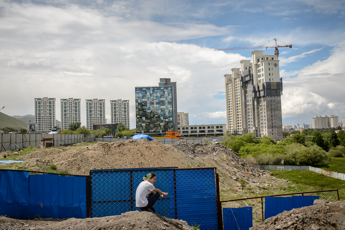 Twenty-two-year old photographer Bilguun, who like many Mongolians uses only one name, sits next to a construction site near his home in one of the luxury high-rise towers in the Zaisan neighbourhood of Ulaanbaatar where he lives with his wife and parents.The economic boom driven by gold, copper and coal mining, sparked an accelerated growth in construction.