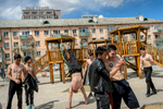 Teenage boys show off their gymnastic skills and tricks in a communal courtyard of Soviet-era buildings in the center of UB.
