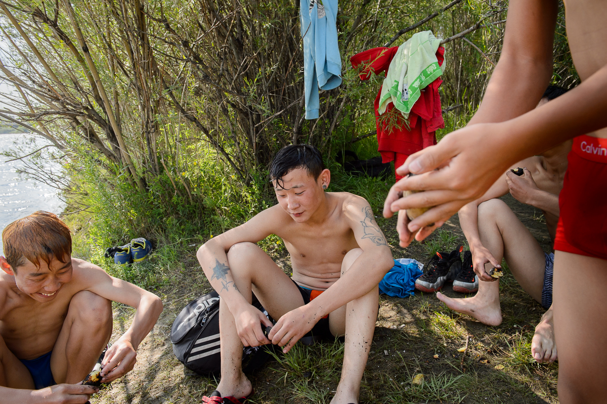 Teenage boys relax after a swim in the polluted river Tuul which runs through the capital.