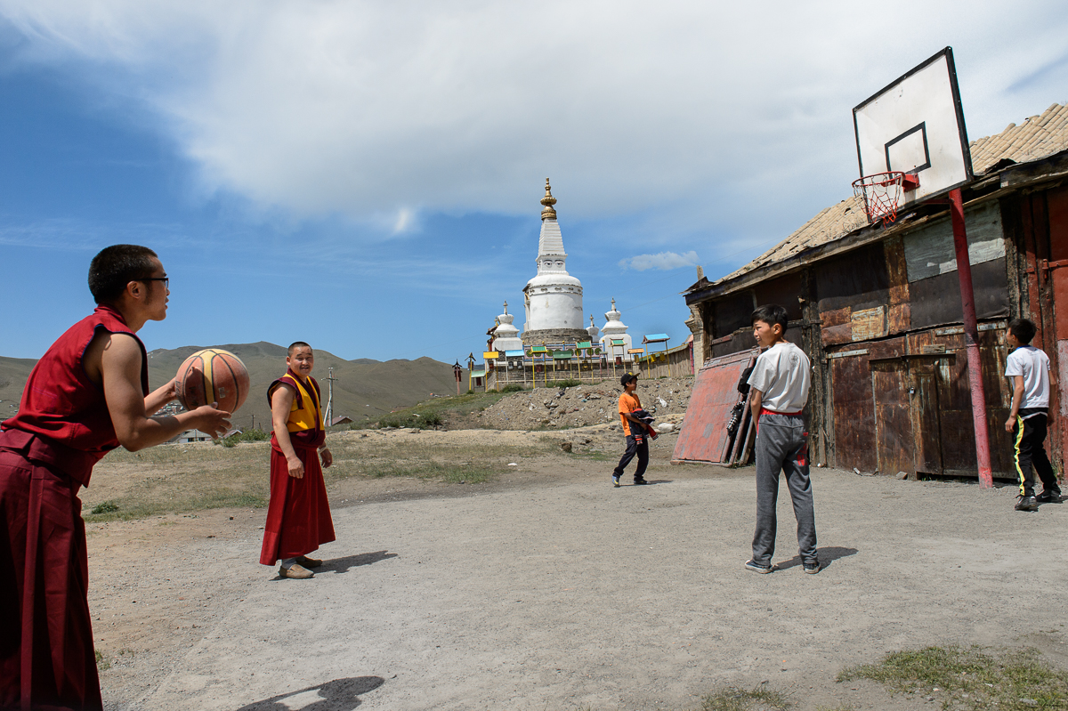 Young Buddhist monks play basketball with local teenage boys at the Dambadarja monastery, located in the north-eastern suburbs of UB. The monastery was among the 1000 Buddhist temples and monasteries that were destroyed or damaged between 1937 and 1939 by Soviet and Mongolian authorities as a supplement to the Soviet Great Purge under Stalin.  After the communist period ended, Buddhism, Mongolia's main religion has experienced a strong resurgence.