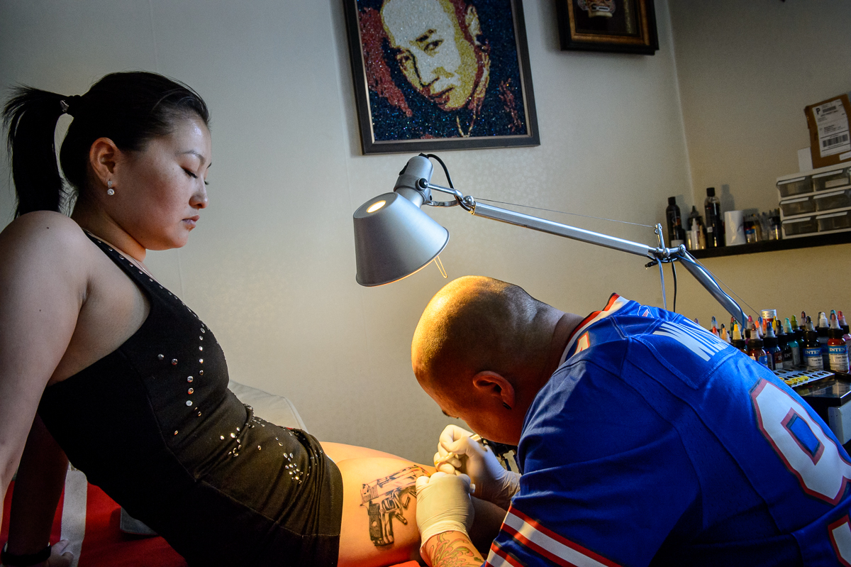 Angie, 24, who until recently lived in Hungary, gets a gun tattoo at Bandgaa's tattoo parlor in UB.  Mongolia's boom has been a magnet to some who left the country years ago.
