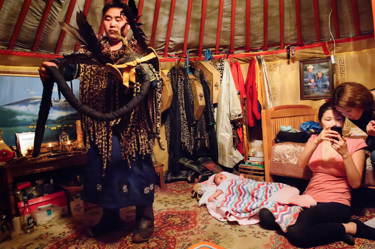 Standing next to his sleeping one-month old son, Otgonbold (27) dresses for a shamanistic ceremony while his wife Anudari (25), a dentist and a shaman as well, shows pictures to her friend Azza.  Although the couple live in an apartment in downtown UB, their shamanistic ceremonies are held in their ger, a round felt tent, set up on the outskirts of the city.