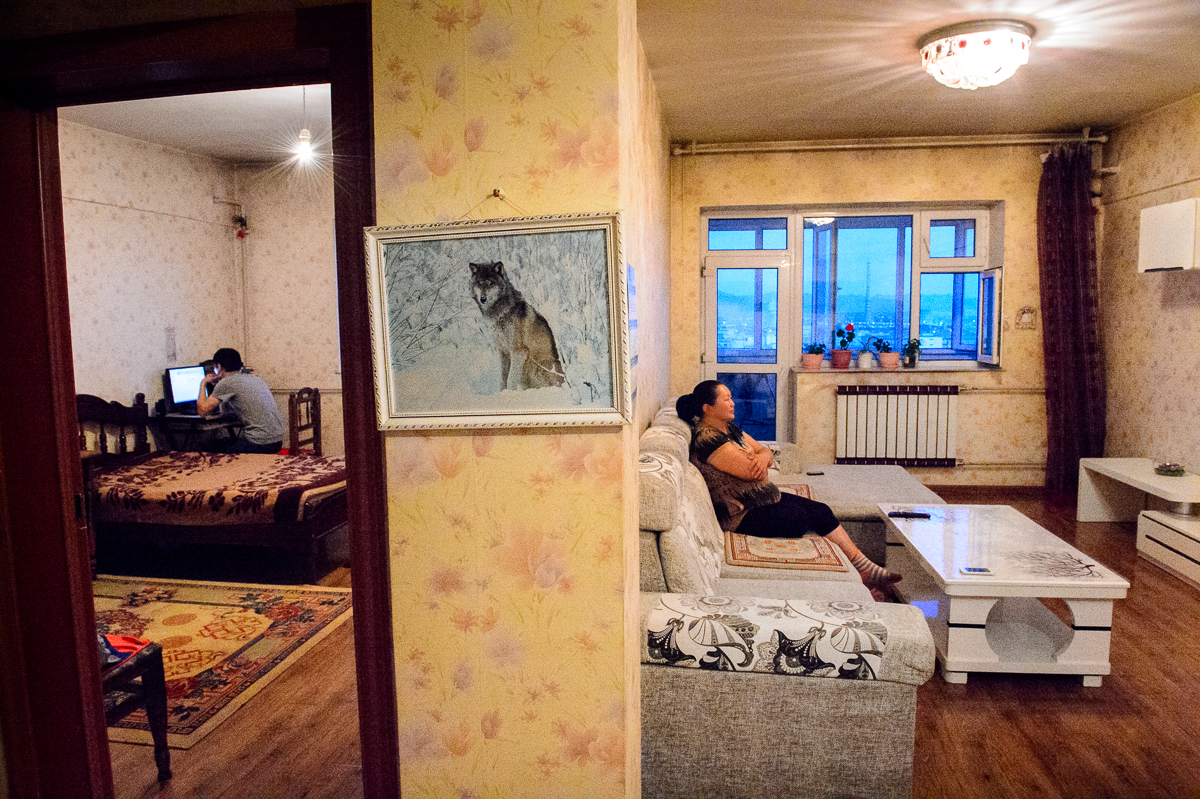 In his bedroom in UB, Batzorig, 25, checks his facebook account while his mother Undarmal sits in the living room of the family's apartment. Mongolian family ties are strong and young people often live at home until they get married.