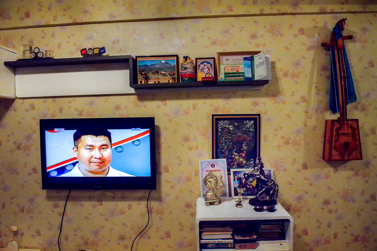The television set in Batzorig's family's home is surrounded by traditional Mongolian and Buddhist objects. After being banned for decades by the Soviet-allied Mongolian Communist Party, Mongolia's main religion knows a revival.