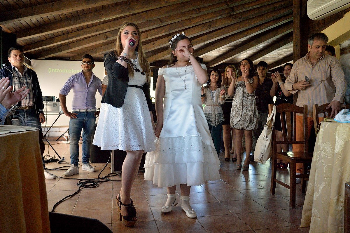 A communion celebration near the town of Caserta. The girl who celebrates her communion is overcome by emotion by the performance of her idol.