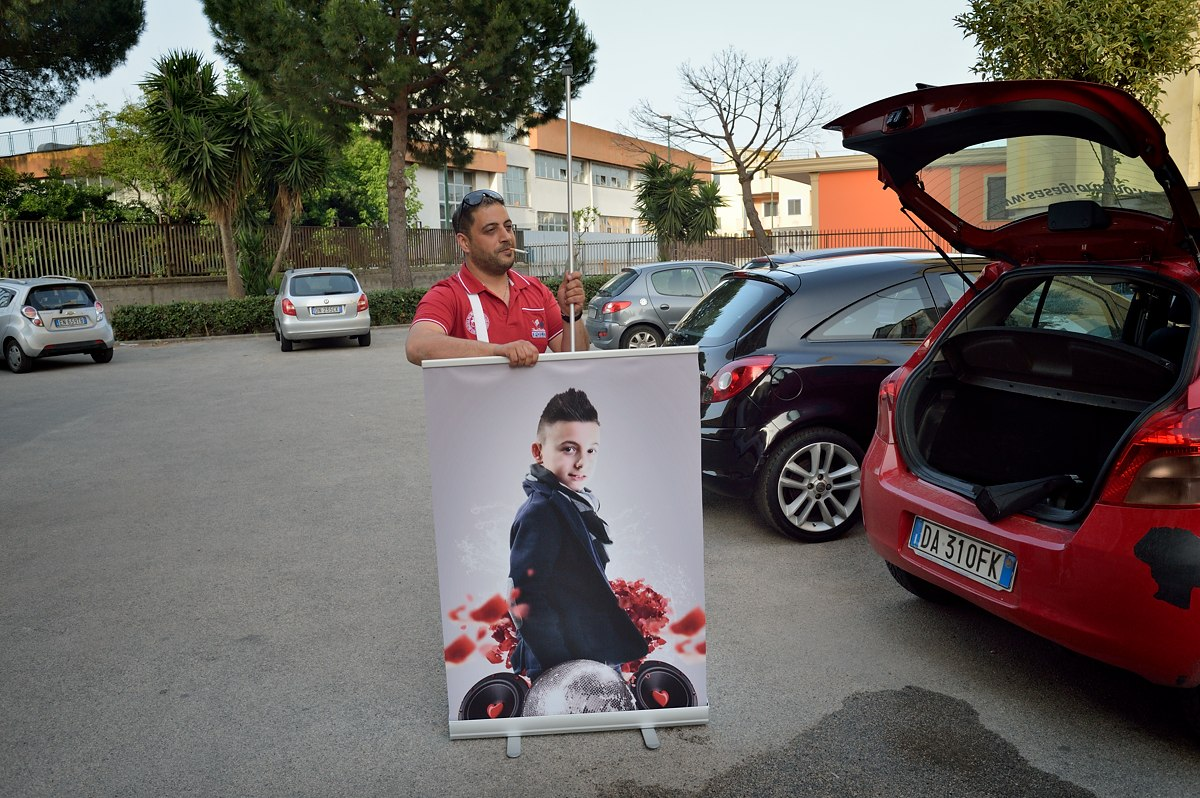 Father-manager Angelo rolls up a poster of Sasà (11). The boy started singing less than a year ago; since then he has recorded a CD and sang at many events. His father promotes him as the new voice from Naples.