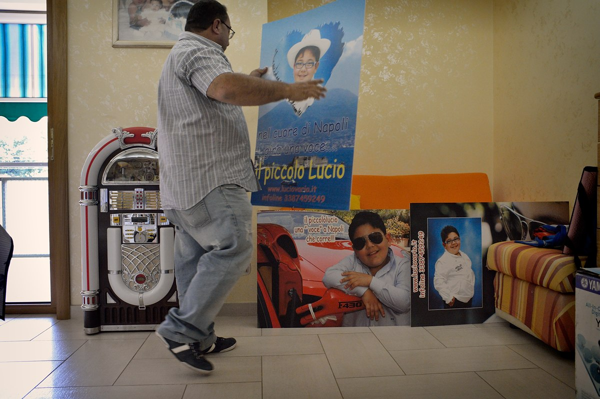 Gaetano holds a cardboard promoting his son Lucio (12) as the voice coming from the heart of Naples.