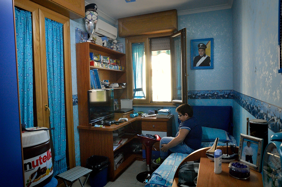 Lucio (12) is seen getting ready for school in his room.
