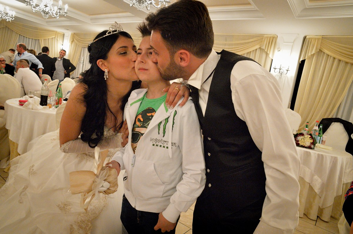 Sasà (11) is kissed by the bride and groom at a wedding celebration held in a lavish banquet hall in Trecase, at the foot of Mount Vesuvius. At a wedding it is not rare to have a succession of both adult and child singers.