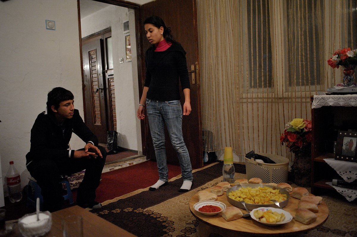 Liridona Hajolli talks to her cousin who joins the family for a typical dinner of potatoes, some pickled vegetables and bread.