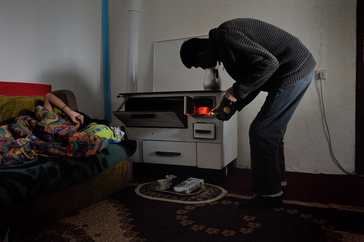 Besim Hajolli tends the wood stove while his daughter Liridona wakes up. Before being expelled in 2010, the Hajolli family lived 15 years in Germany.
