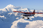 Paul Rodderick flies a Talkeetna Air Taxi 'turbine otter' over the Alaska Range with Denali and Mt. Hunter in the background. Alaska