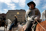 Cowboys joke before riding in the Chinese New Year's Parade in Astoria, Queens.--The Federation of Black Cowboys is a nonprofit fraternal organization headquartered at a ranch straddling the Brooklyn- Queens line in New York City. As a 501(c)3 organization, they {quote}seek to create greater understanding of African American culture and heritage{quote} and {quote}endeavor to provide educational opportunities for the young public of New York.{quote} There are around 35 Federation members, all committed to keeping alive the history of African Americans like Nat Love, Bill Pickett, and Stagecoach Mary Fields in the old West.Federation membership ranges from former insurance salesmen and city transit workers to former rodeo stars and rural transplants. Founded in 1994, the organization is headquartered at Cedar Lane Stables in Howard Beach, Queens. One of the ways in which the Federation engages with the community is through a Saturday program for at-risk youth. Each Saturday for an entire semester, a class of students is bussed to the ranch to attend mandatory educational sessions with topics ranging from respect and self-esteem to horse care and riding. Most of the program's young participants have never seen a horse in person before, let alone touched or rode one.