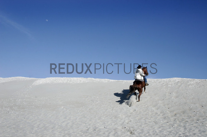 A Federation member rides up a sand dune at Floyd Bennett FIeld in Brooklyn, New York.--The Federation of Black Cowboys is a nonprofit fraternal organization headquartered at a ranch straddling the Brooklyn- Queens line in New York City. As a 501(c)3 organization, they {quote}seek to create greater understanding of African American culture and heritage{quote} and {quote}endeavor to provide educational opportunities for the young public of New York.{quote} There are around 35 Federation members, all committed to keeping alive the history of African Americans like Nat Love, Bill Pickett, and Stagecoach Mary Fields in the old West.Federation membership ranges from former insurance salesmen and city transit workers to former rodeo stars and rural transplants. Founded in 1994, the organization is headquartered at Cedar Lane Stables in Howard Beach, Queens. One of the ways in which the Federation engages with the community is through a Saturday program for at-risk youth. Each Saturday for an entire semester, a class of students is bussed to the ranch to attend mandatory educational sessions with topics ranging from respect and self-esteem to horse care and riding. Most of the program's participants have never seen a horse in person before, let alone touched or rode one.