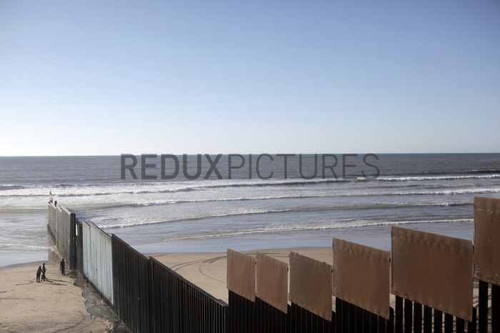 Visitors in Mexico look through the border wall into the United States, where the wall ends in the Pacific Ocean.
