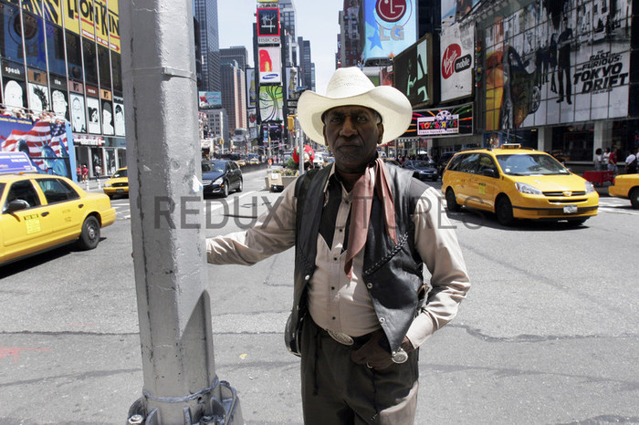 Cowboy Al stands for a picture in Times Square before stopping for tea at his favorite Au Bon Pain near Macy's.--The Federation of Black Cowboys is a nonprofit fraternal organization headquartered at a ranch straddling the Brooklyn- Queens line in New York City. As a 501(c)3 organization, they {quote}seek to create greater understanding of African American culture and heritage{quote} and {quote}endeavor to provide educational opportunities for the young public of New York.{quote} There are around 35 Federation members, all committed to keeping alive the history of African Americans like Nat Love, Bill Pickett, and Stagecoach Mary Fields in the old West.Federation membership ranges from former insurance salesmen and city transit workers to former rodeo stars and rural transplants. Founded in 1994, the organization is headquartered at Cedar Lane Stables in Howard Beach, Queens. One of the ways in which the Federation engages with the community is through a Saturday program for at-risk youth. Each Saturday for an entire semester, a class of students is bussed to the ranch to attend mandatory educational sessions with topics ranging from respect and self-esteem to horse care and riding. Most of the program's participants have never seen a horse in person before, let alone touched or rode one.