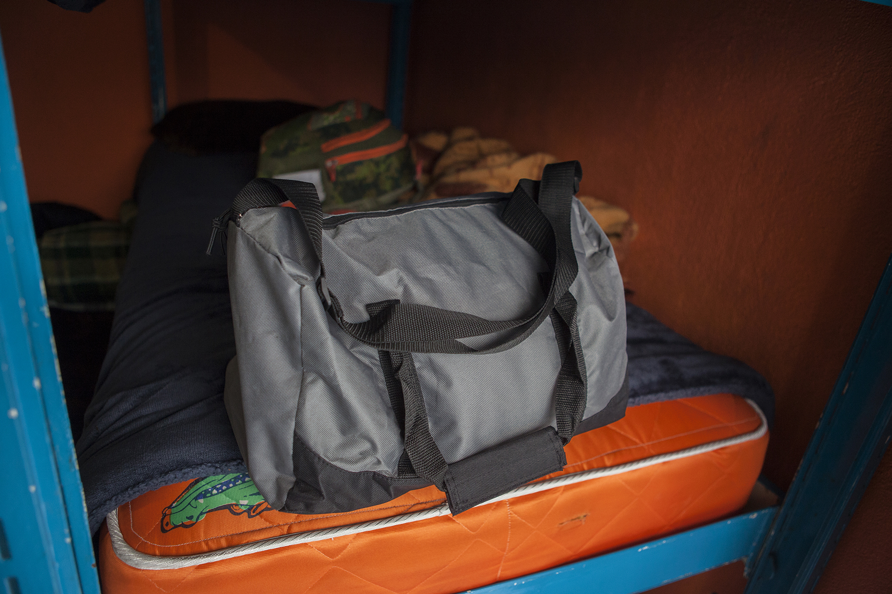 Unaccompanied child and teenage migrants like Vladi from El Salvador, whose duffle bag of possessions is shown here, stay in Tijuana, Mexico's only shelter for minors on November 29, 2018. CREDIT: Erin Siegal McIntyre for Frontline