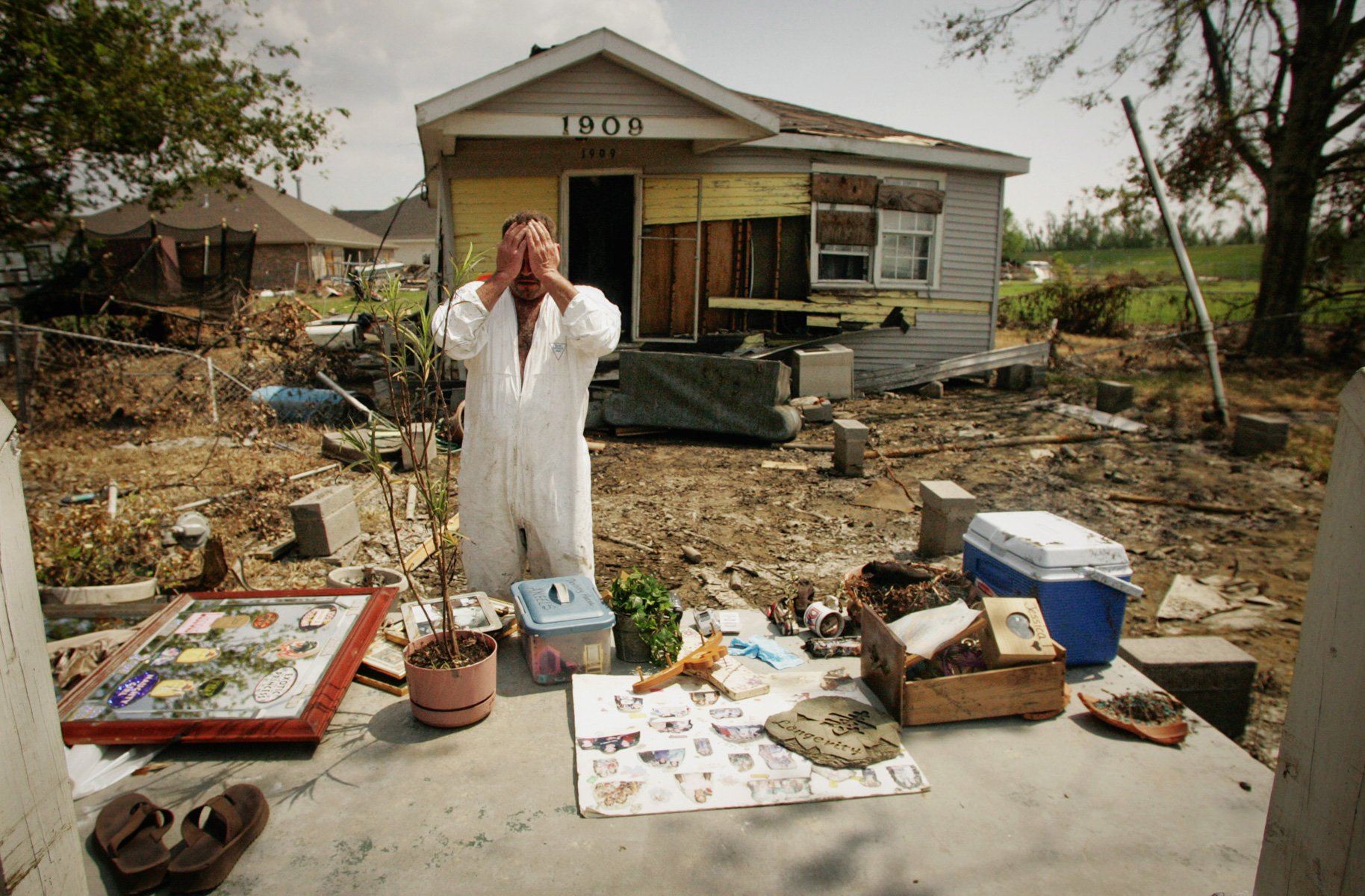 Untitled - Steve Minyard (cq) stands in the place where his house once stood September 16, in Meraux, La.  Spread out on stoop are all the items which he could salvage from the wreckage left after the wind and flooding of Hurricane Katrina.  Among the keepsakes Minyard was especially intent on finding were pictures of his sister who died little over a year ago.  Minyard shared the house in St. Bernard Parish with his fiancee Jessica Marques Piazza and the two had returned Friday to gather their belongings.  {quote}To some people this doesn't seem like much,{quote} Piazza said.  {quote}But this is all I had.  All I had.{quote}  The couple does not have any insurance.